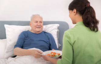 Graceworks at Home client served lunch in bed by aide