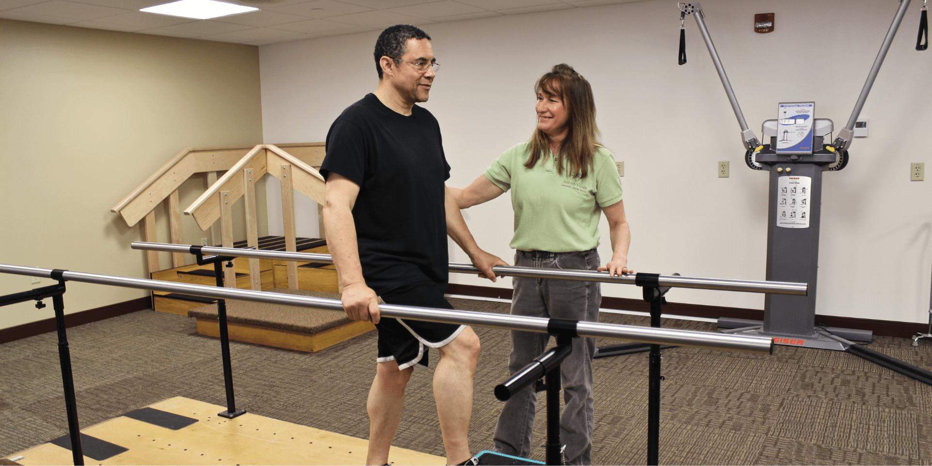 Bethany Rehab Center patient with aide walking with parallel bars