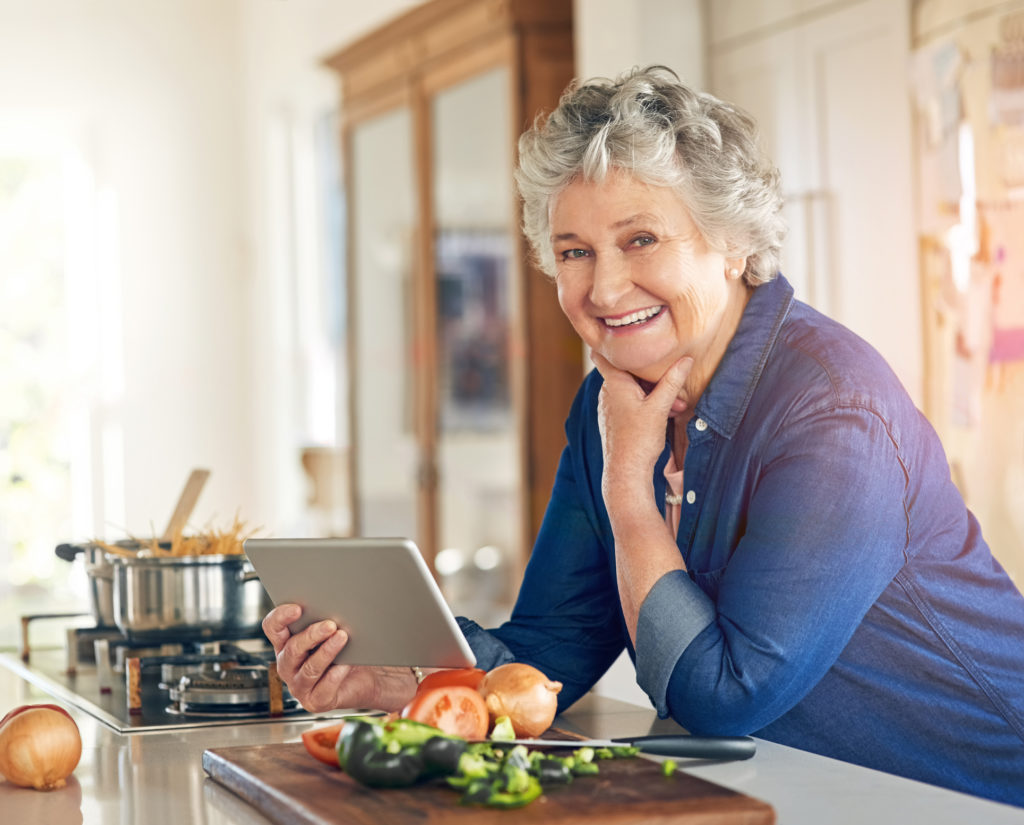 Older woman in kitchen using tablet while cooking