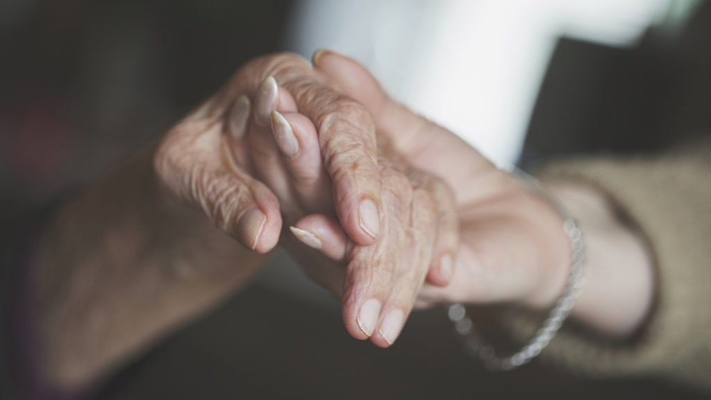 Close up of senior hand being held by younger hand.