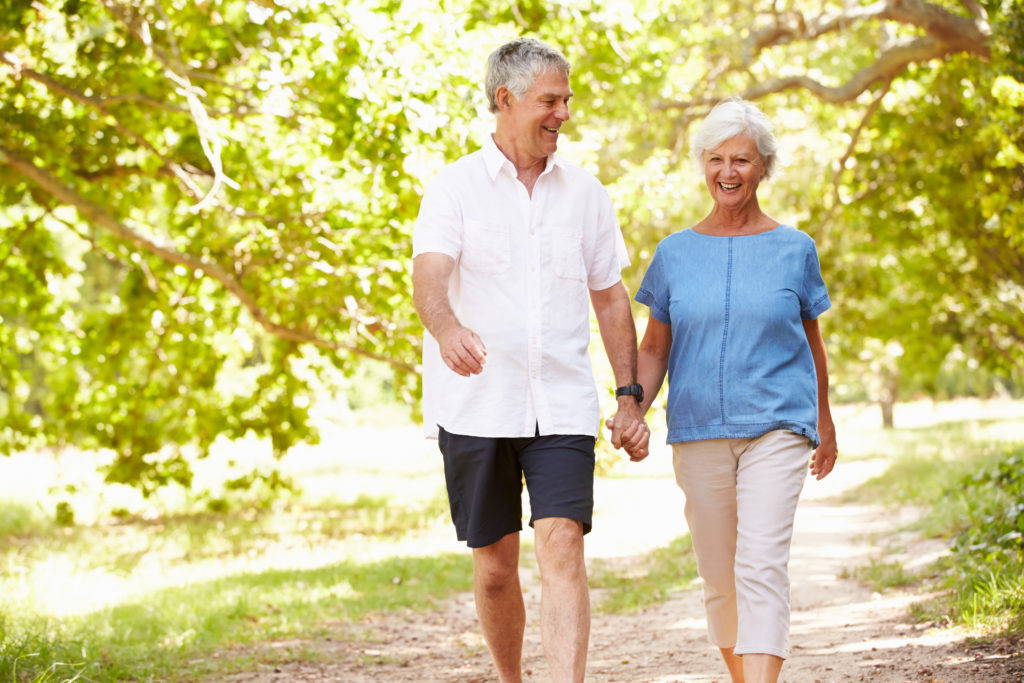 Senior couple walking on a path together in the countryside