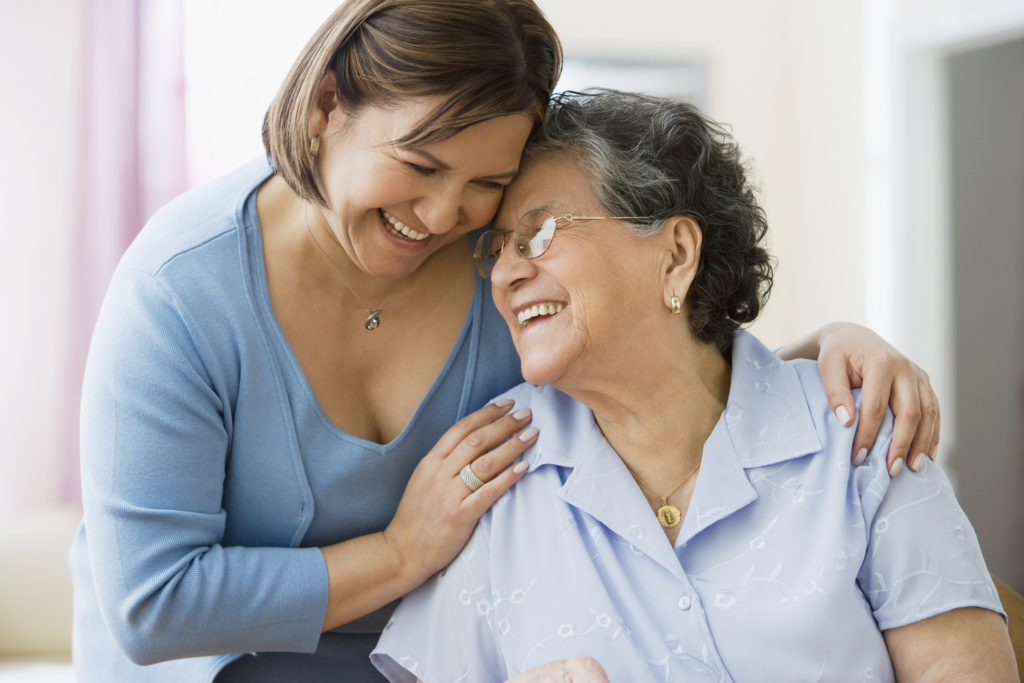 Middle-aged woman hugging older woman