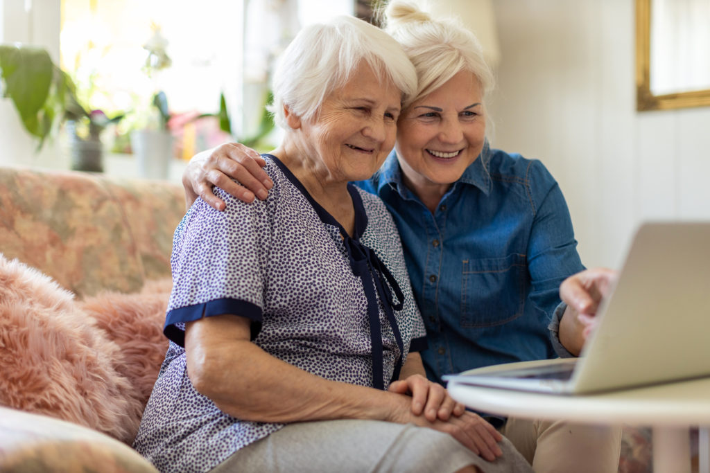 Adult daughter teaching her elderly mother to use laptop