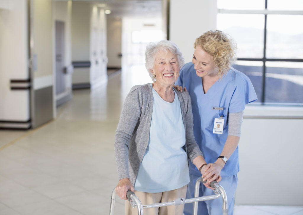Nurse helping senior patient with walker in hospital corridor